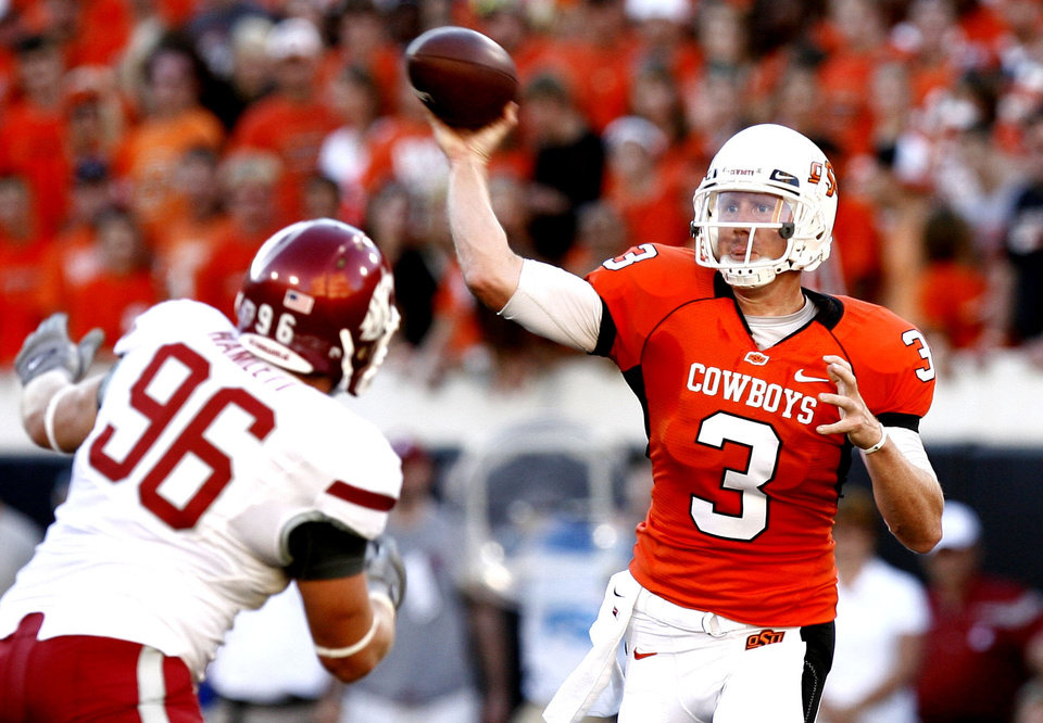 Photo - OSU's Brandon Weeden (3) throws a pass as WSU's Casey Hamlett (96) pressures him during the college football game between the Washington State Cougars (WSU) and the Oklahoma State Cowboys (OSU) at Boone Pickens Stadium in Stillwater, Okla., Saturday, September 4, 2010. Photo by Sarah Phipps, The Oklahoman