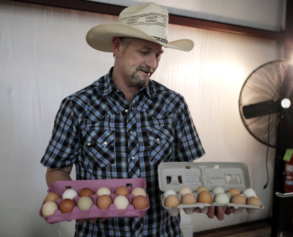 Photo - Darren Holly of Twisted Feather Farms shows two cartons of eggs that can be bought at his booth at the farmer's market on the campus of OSU-OKC on June 5, 2013. Photo by KT KING, The Oklahoman
