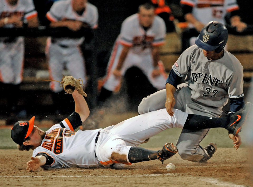Photo - UC Irvine infielder Chris Rabago, right collides with Oklahoma State pitcher Jon Perrin after scoring during the fifth inning of an NCAA college baseball super regional tournament game in Stillwater, Okla, Friday, June 6, 2014. (AP Photo/Brody Schmidt)