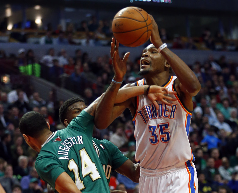 Oklahoma City Thunder forward Kevin Durant (35) has the ball strip from him by Chicago Bulls guard D.J. Augustin (14) during the first half of an NBA basketball Monday, March 17, 2014, in Chicago.  (AP Photo/Jeff Haynes)
