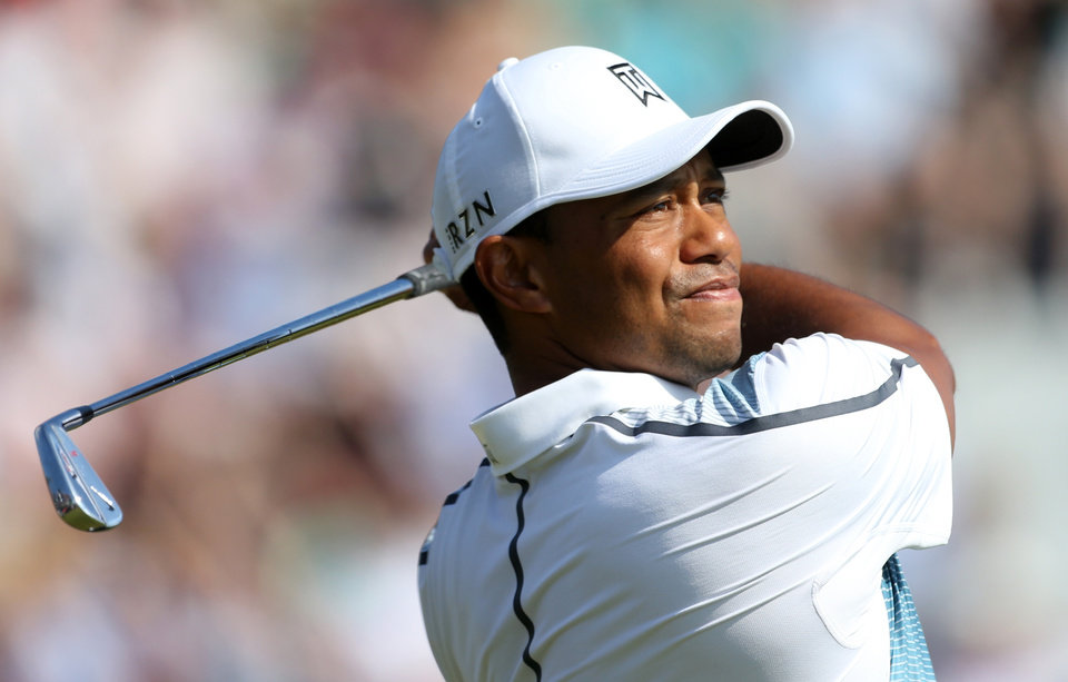 Photo - Tiger Woods of the US plays a shot off the 4th tee during the first day of the British Open Golf championship at the Royal Liverpool golf club, Hoylake, England, Thursday July 17, 2014. (AP Photo/Peter Morrison)