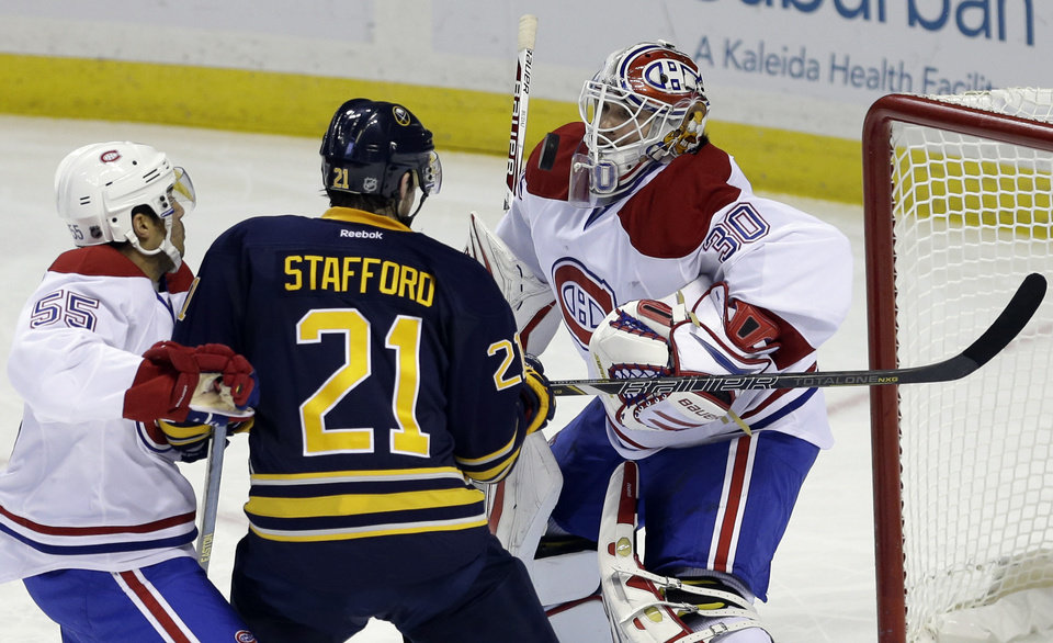 Buffalo Sabres' Drew Stafford (21) battles for the puck with Montreal Canadiens' Francis Bouillon (55) in front of goalie Peter Budaj, of Switzerland, during the first period of an NHL hockey game in Buffalo, N.Y., Thursday, Feb. 7, 2013. (AP Photo/David Duprey)