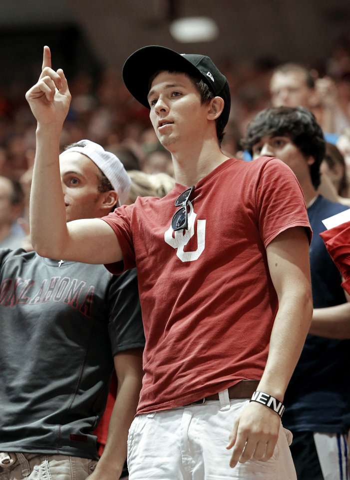 Photo - Freshman Aaron Kalivas, of Broken Arrow, raises his hand Thursday during a fight song before the University of Oklahoma's New Sooner Convocation.  Photo by Steve Sisney,  The Oklahoman