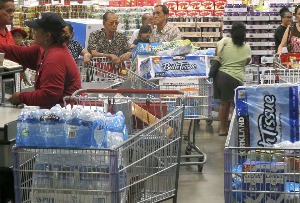 Photo - Shoppers stock up on cases of bottled water and other supplies in preparation for a hurricane and tropical storm heading toward Hawaii at the Iwilei Costco in Honolulu on Tuesday, Aug. 5, 2014. Two big storms so close together is rare in the eastern Pacific, and Hurricane Iselle could make landfall by Friday and Tropical Storm Julio could hit two or three days later, weather officials said. (AP Photo/Audrey McAvoy)