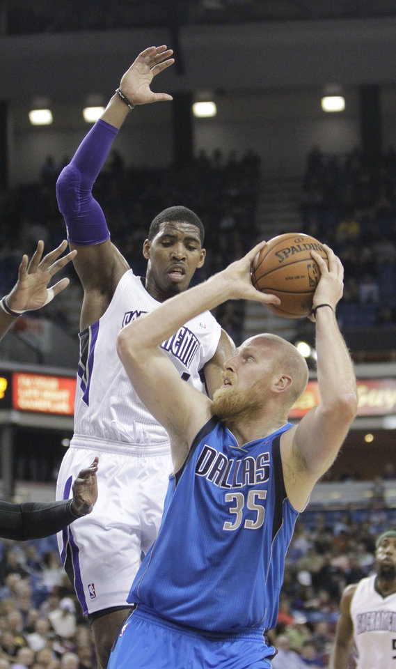 Sacramento Kings forward Jason Thompson, left, leaps as Dallas Mavericks center Chris Kaman prepares to shoot during the first quarter of an NBA basketball game in Sacramento, Calif., Friday, April 5, 2013. (AP Photo/Rich Pedroncelli)
