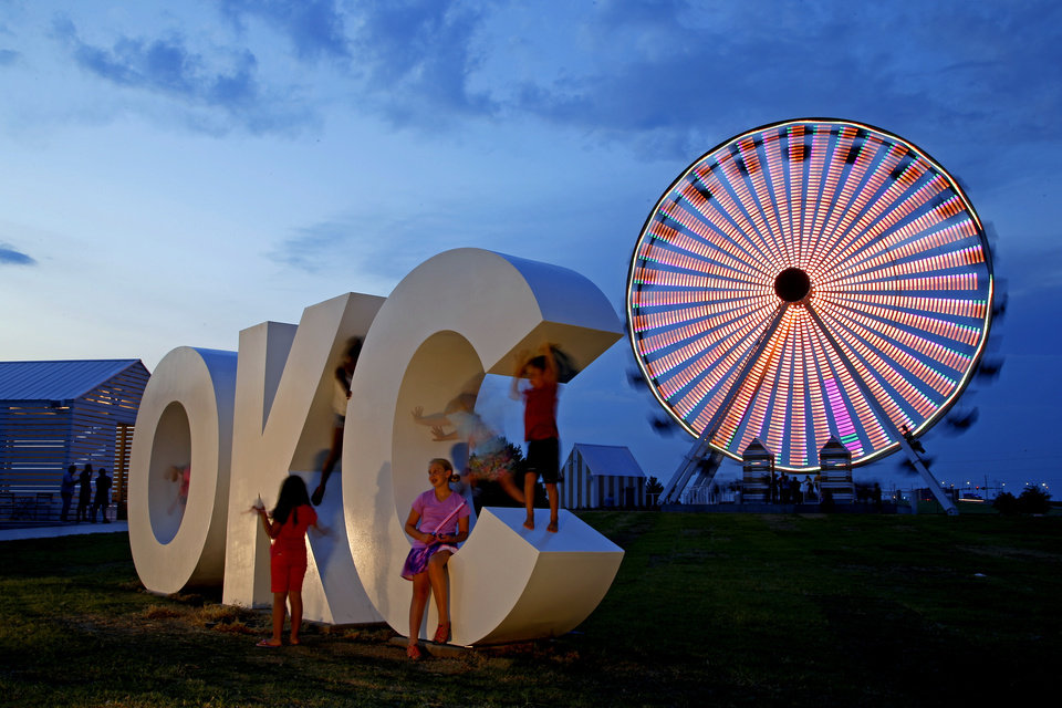 Photo -  People play Thursday on an OKC sculpture in front of the Wheeler Ferris wheel in Oklahoma City during a testing event. [Photo by Bryan Terry, The Oklahoman]