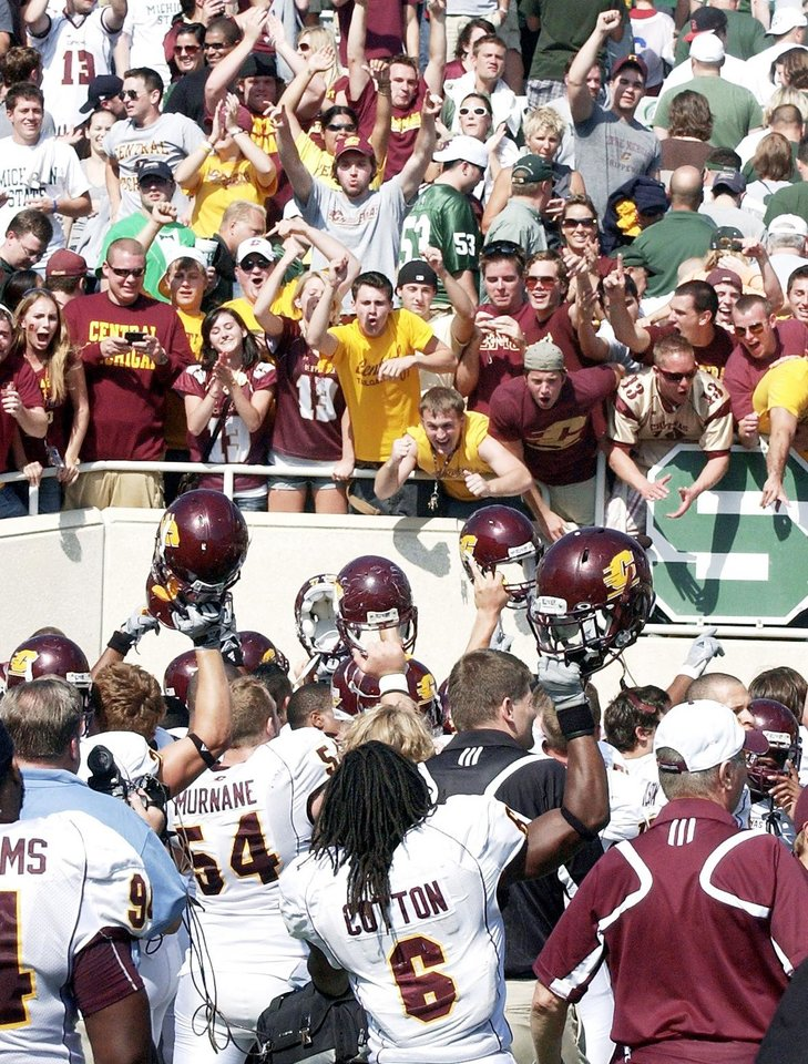 Photo - Central Michigan players hold up their helmets to fans after upsetting Michigan State on Saturday.  AP Photo