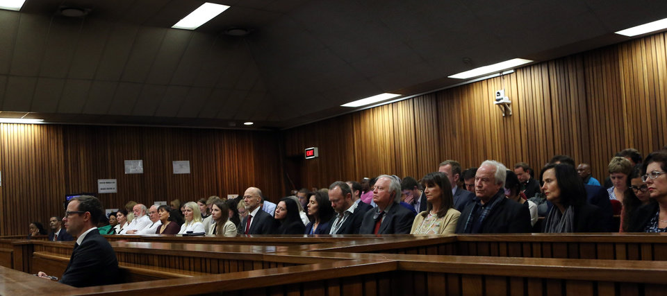 Photo - Oscar Pistorius, left, sits in court during his trial, in Pretoria, South Africa, Friday, Aug. 8, 2014. The chief defense lawyer for Pistorius delivered final arguments in the athlete's  trial on Friday, alleging that Pistorius thought he was in danger when he killed girlfriend Reeva Steenkamp and also that police mishandled evidence at the house where the shooting happened. (AP Photo/Themba Hadebe, Pool)
