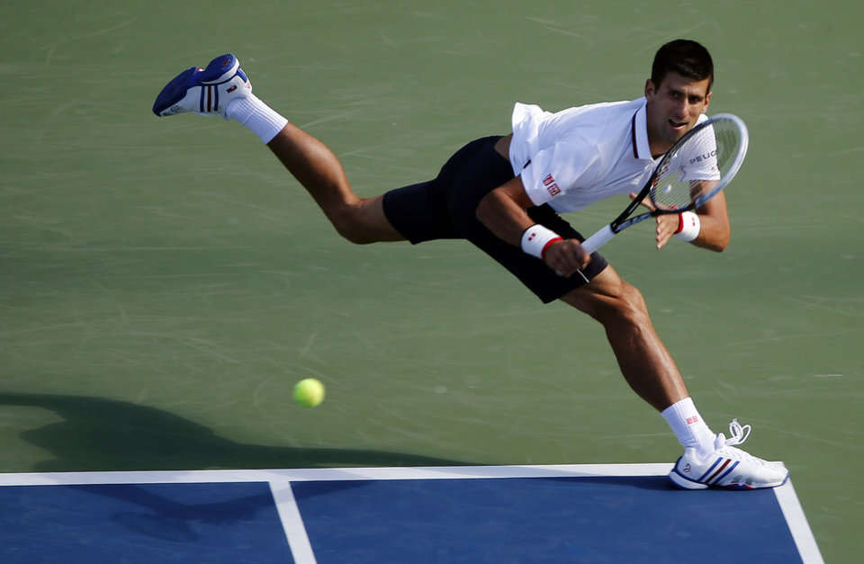 Photo - Novak Djokovic, of Serbia, returns a shot to Paul-Henri Mathieu, of France, during the second round of the 2014 U.S. Open tennis tournament, Thursday, Aug. 28, 2014, in New York. (AP Photo/Elise Amendola)
