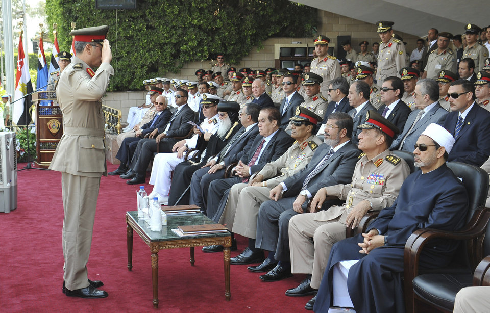 Photo -   In this image released by the Egyptian President, an Egyptian military officer salutes President Mohammed Morsi, third from right, as he sits with Prime Minister Kamal el-Ganzouri, center, Field Marshal Hussein Tantawi, fourth right, Army Chief of Staff Gen. Sami Anan, second right, and the Grand Sheik of Al-Azhar, Ahmed el-Tayyib, right, at a graduation ceremony at a military base east of Cairo, Egypt, Monday, July 9, 2012. Egypt's highest court insisted Monday that its ruling that led to the dissolution of the Islamist-dominated parliament was final and binding, setting up a showdown with the country's newly elected president. The announcement on state TV came a day after President Mohammed Morsi recalled the legislators, defying the powerful military's decision to dismiss parliament after the Supreme Constitutional Court ruled that a third of its members had been elected illegally.(AP Photo/Sheriff Abd El Minoem, Egyptian Presidency)