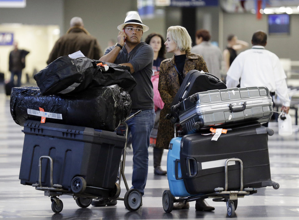 FILE - In this Dec. 1, 2013 file photo, travelers walk through terminal 3 baggage claim at O'Hare International airport in Chicago. The government reported Monday, May 5, 2014, that U.S. airlines raised $3.35 billion from bag fees in 2013, down 4 percent from 2012. That�s the biggest decline since fees to check a bag or two took off in 2008. (AP Photo/Nam Y. Huh, File)