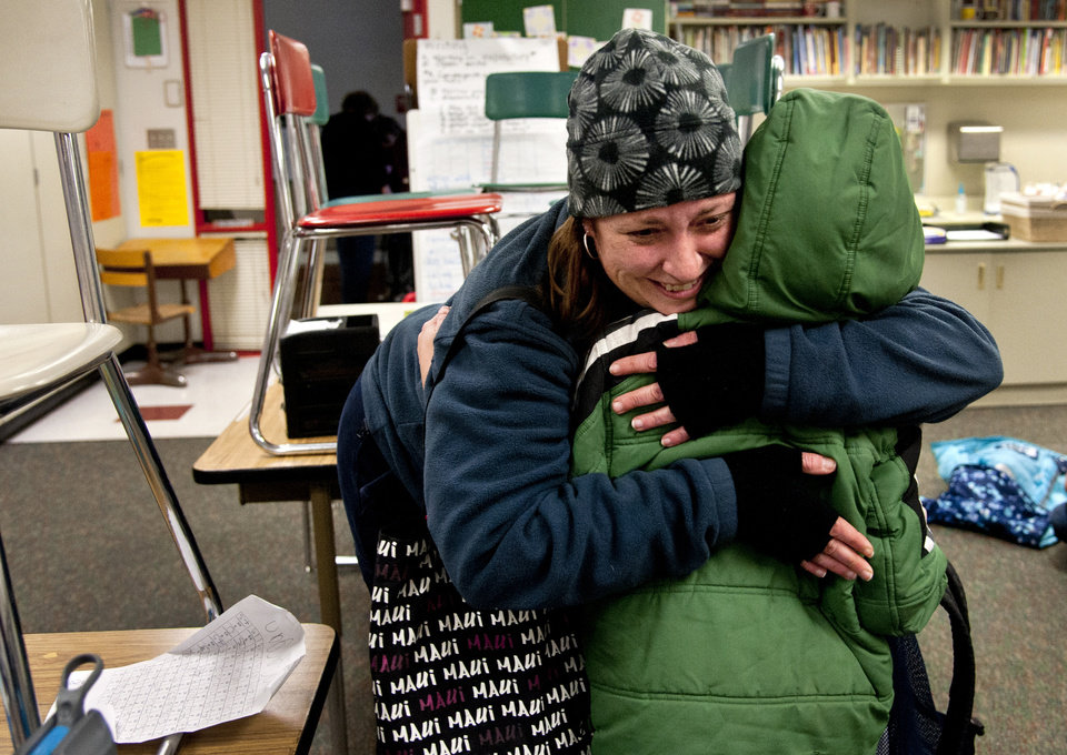 Photo - After watching TV news reports of the school shooting in Connecticut, Alicia Combo tightly hugs her son Morgan Askins at the close of school, Dec. 14, 2012, at Garfield Elementary in Spokane, Wash. A man killed his mother at their home and then opened fire Friday inside the elementary school where she taught, massacring 26 people, including 20 children, as youngsters cowered in fear to the sound of gunshots reverberating through the building and screams echoing over the intercom. (AP Photo/Spokesman Review, Dan Pelle)