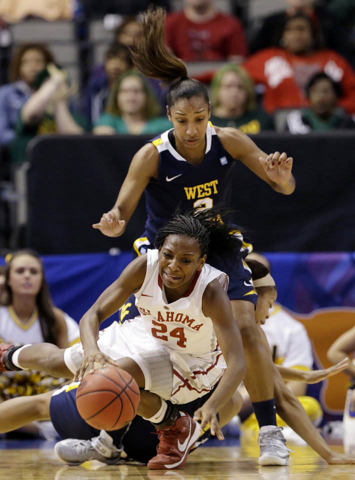 Photo - Oklahoma's Sharane Campbell (24) maintains control of the ball as she is knocked down by West Virginia' Christal Caldwell, bottom rear, as Taylor Palmer (2) watches in the first half of an NCAA college basketball game at the Big 12 Conference women's tournament Saturday, March 9, 2013, in Dallas. (AP Photo/Tony Gutierrez)