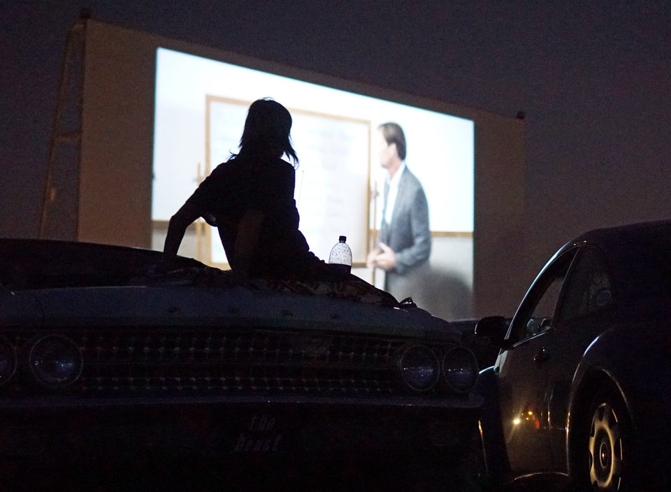 Photo - Jana McElyea watches the movie from the trunk of her car at the Airline Drive-in movie theater in Ponca City Thursday, August 14, 2014. Photo by Doug Hoke, The Oklahoman