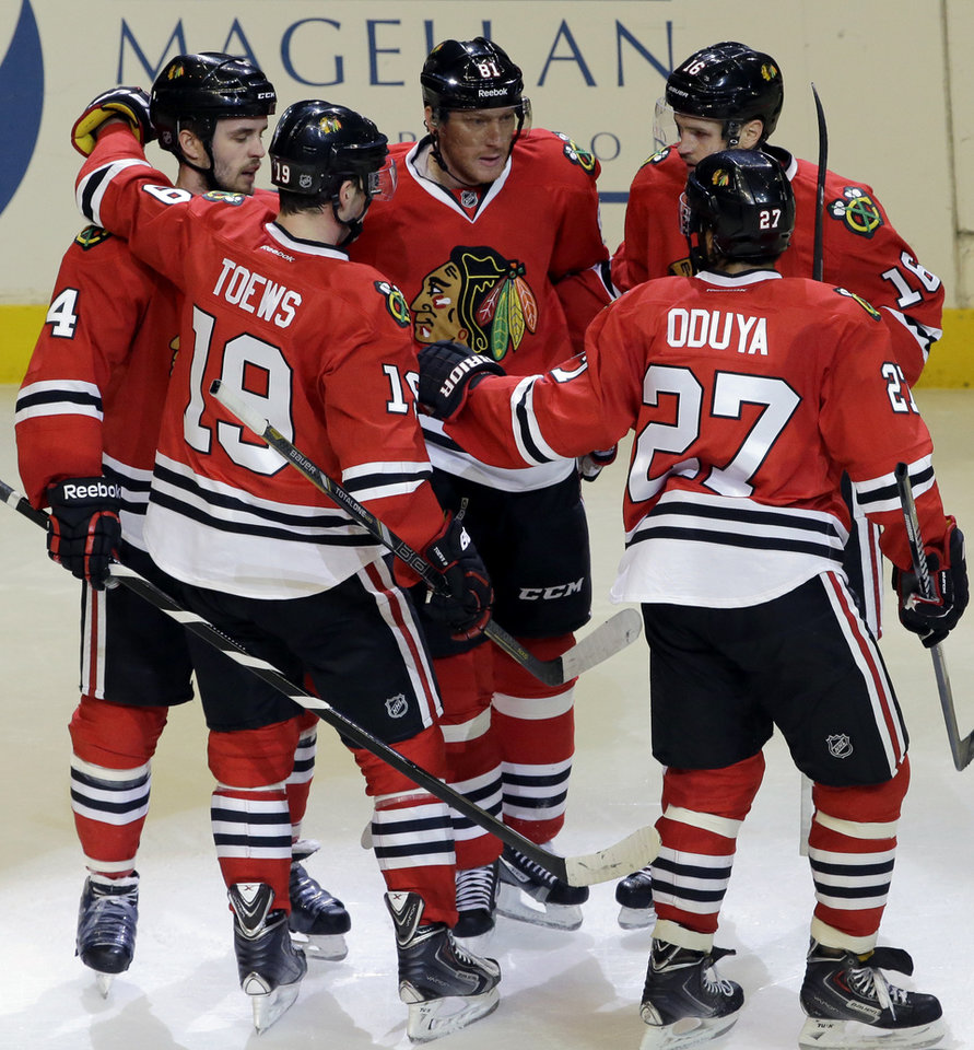 Photo - Chicago Blackhawks' Marian Hossa, center, celebrates with teammates after scoring his second goal, during the third period of an NHL hockey game against the Anaheim Ducks in Chicago, Friday, Jan. 17, 2014. The Blackhawks won 4-2. (AP Photo/Nam Y. Huh)