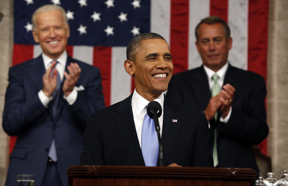 Photo - President Barack Obama delivers the State of Union address before a joint session of Congress in the House chamber Tuesday, Jan. 28, 2014, in Washington, as Vice President Joe Biden, and House Speaker John Boehner of Ohio, applaud. (AP Photo/Larry Downing, Pool)
