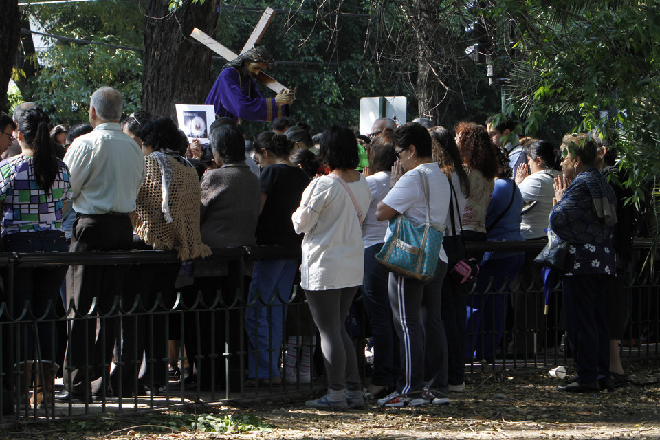 Photo - People who were participating in a Holy Week procession stop and pray after a strong earthquake jolted Mexico City, Friday, April 18, 2014. A powerful magnitude-7.2 earthquake shook central and southern Mexico but there were no early reports of major damage or casualties. (AP Photo/Marco Ugarte)