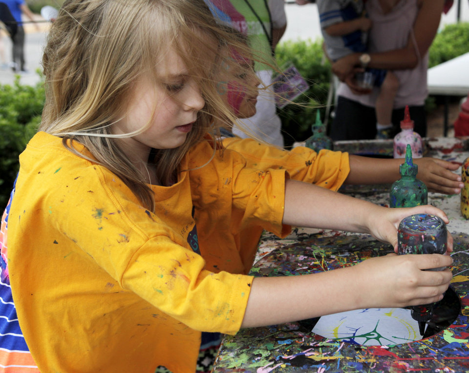 Photo -  Reagan Jones makes art on a spinning canvas in a booth for children at the 2013 Paseo Arts Festival. Photo by K.T. King, The Oklahoman Archives   KT King -