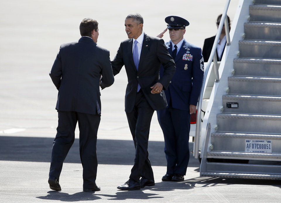 Photo - Denison Mayor Jared Johnson, left, greets President Barack Obama after his arrival at the North Texas Regional Airport in Denison, Texas, Wednesday, July 15, 2015. (AP Photo/Tony Gutierrez)