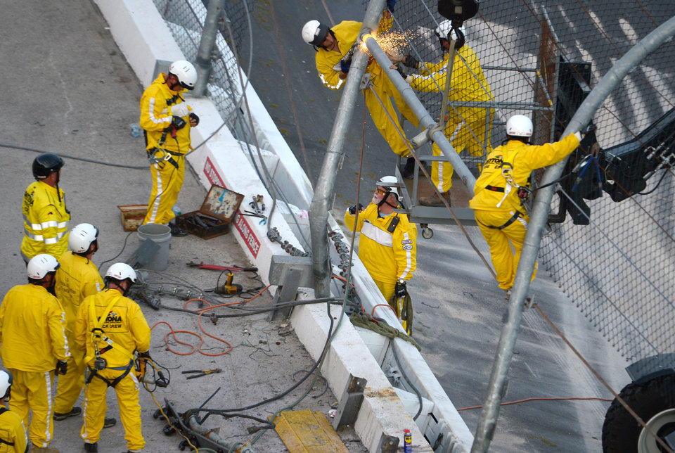 Photo - Track workers repair the safety fence along on the front grandstands, where Kyle Larson's car hit it on the final lap of the NASCAR Nationwide Series auto race at Daytona International Speedway in Daytona Beach, Fla., Saturday, Feb. 23, 2013. (AP Photo/Phelan M. Ebenhack)