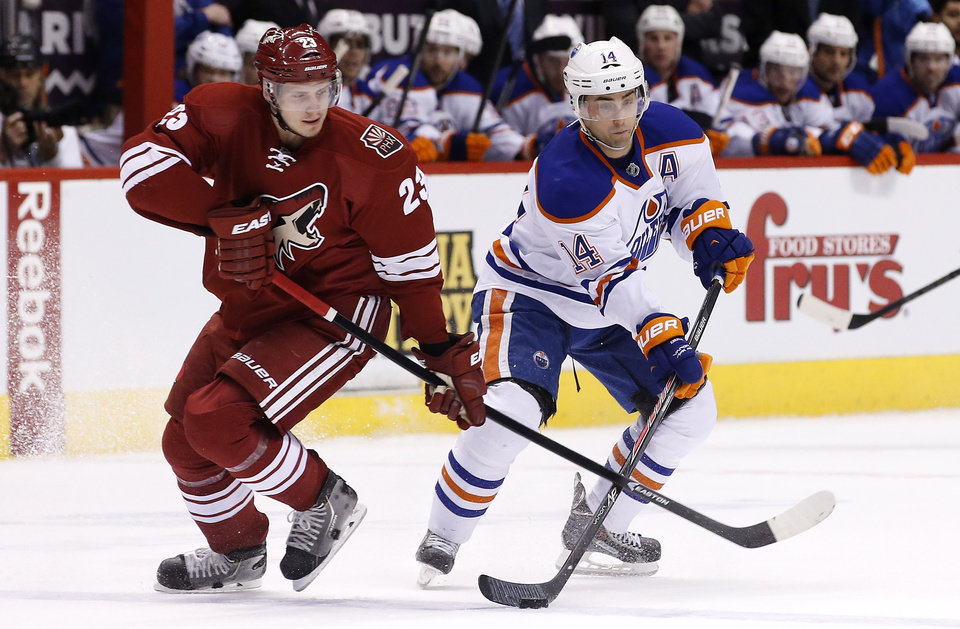Photo - Phoenix Coyotes' Oliver Ekman-Larsson (23), of Sweden, slaps the stick of Edmonton Oilers' Jordan Eberle (14) as Eberle tries to make a pass during the first period of an NHL hockey game, Friday, April 4, 2014, in Glendale, Ariz. (AP Photo/Ross D. Franklin)