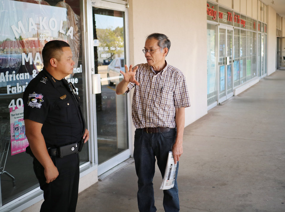 Photo -  Oklahoma County sheriff's deputy Tom Ly, with the Community Services Division, talks with Long Nguyen, owner of Pho Ca Dao Vietnamese Noodle House. [Photos by Doug Hoke, The Oklahoman]