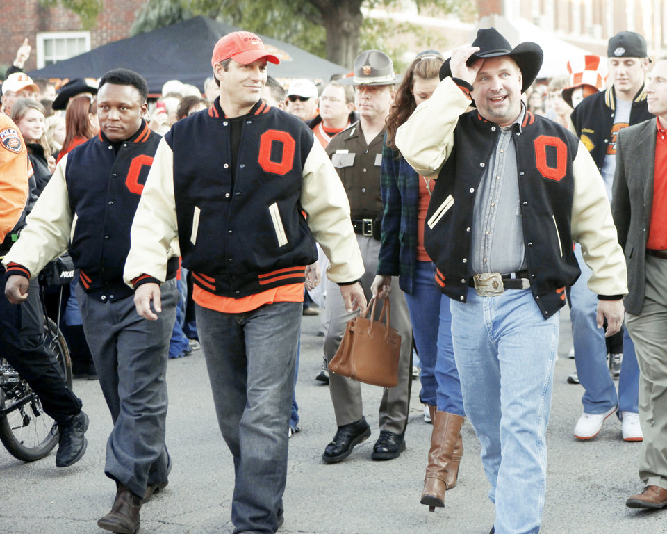 Photo - Barry Sanders, Robin Ventura and Garth Brooks wave to the crowd during the walk to the stadium before the Cowboys' game against Missouri on Saturday.  Photo by Doug Hoke, The Oklahoman