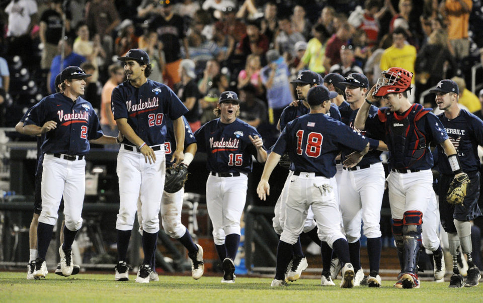 Photo - Vanderbilt players celebrate after Vanderbilt defeated Virginia 9-8 in the opening game of the best-of-three NCAA baseball College World Series finals in Omaha, Neb., Monday, June 23, 2014. (AP Photo/Eric Francis)