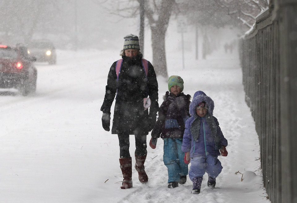 Photo - Linda Jones walks her daughters Sophie and Zoe to school as a blizzard dropped snow over Boulder, Colo., Wednesday Dec. 19, 2012. A storm that has dumped more than a foot of snow in the Rocky Mountains is heading east and is forecast to bring the first major winter storm of the season to the central plains and Midwest. (AP Photo/Brennan Linsley)