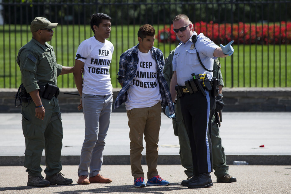 Photo - Demonstrators are arrested outside the White House in Washington, Thursday, Aug. 28, 2014, during an immigration reform demonstration. With impeachment threats and potential lawsuits looming, President Barack Obama knows whatever executive actions he takes on immigration will face intense opposition. So as a self-imposed, end-of-summer deadline to act approaches, Obama's lawyers are carefully crafting a legal rationale they believe will withstand scrutiny and survive any court challenges, administration officials say. (AP Photo/Evan Vucci)