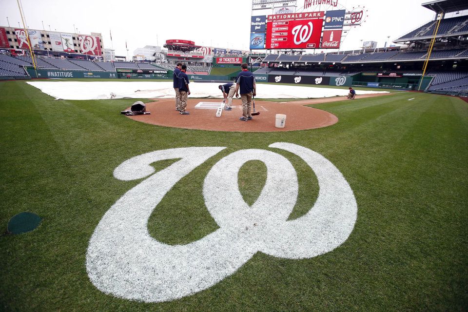 Photo - The grounds crew readies the field before an exhibition baseball game between the Washington Nationals and the Detroit Tigers at Nationals Park Saturday, March 29, 2014, in Washington. (AP Photo/Alex Brandon)
