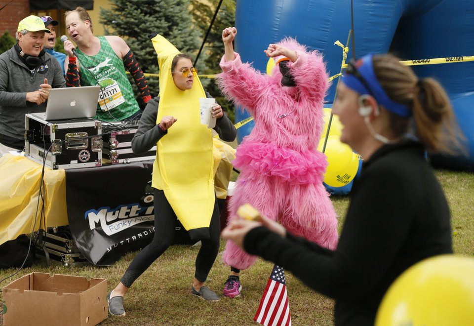 Photo - Susan Phillips, in the gorilla costume, and Bridget Roush, in the banana costume, dance along Gorilla Hill near NW 40 and Shartel Ave. during the the Oklahoma City Memorial Marathon in Oklahoma City, Sunday, April 30, 2017. Photo by Nate Billings, The Oklahoman