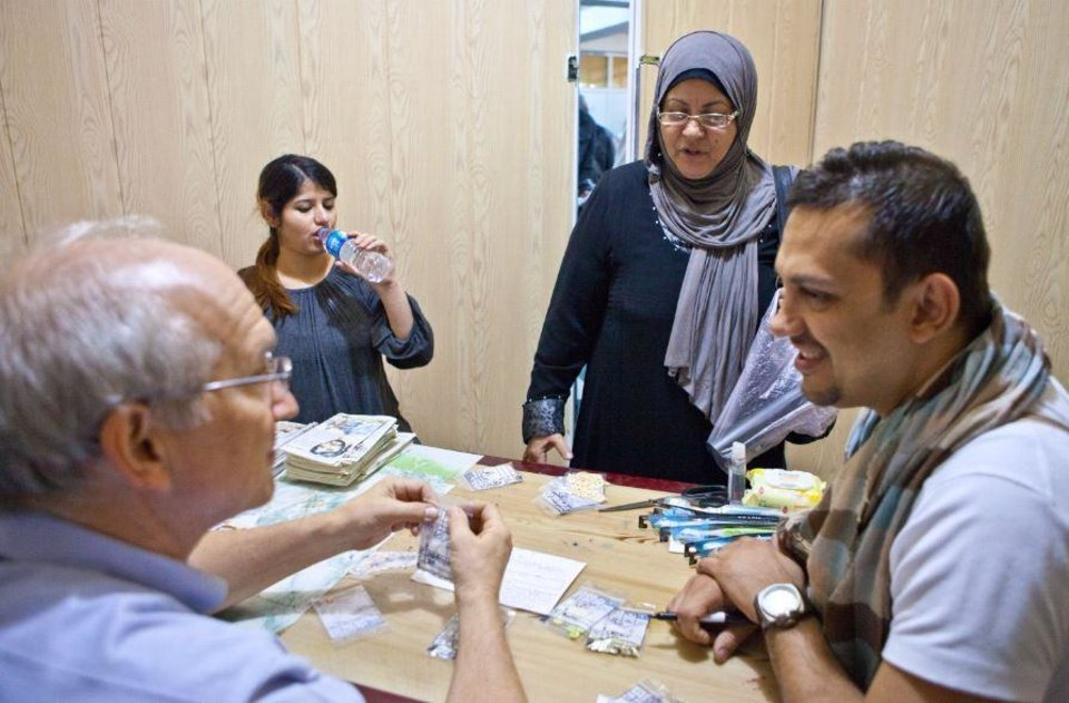 Photo -  Dr. Chris Jenkins, left, works with an Iraqi translator to distribute medication to refugees in Iraq.   Whittenburger, Valerie -  Photo provided
