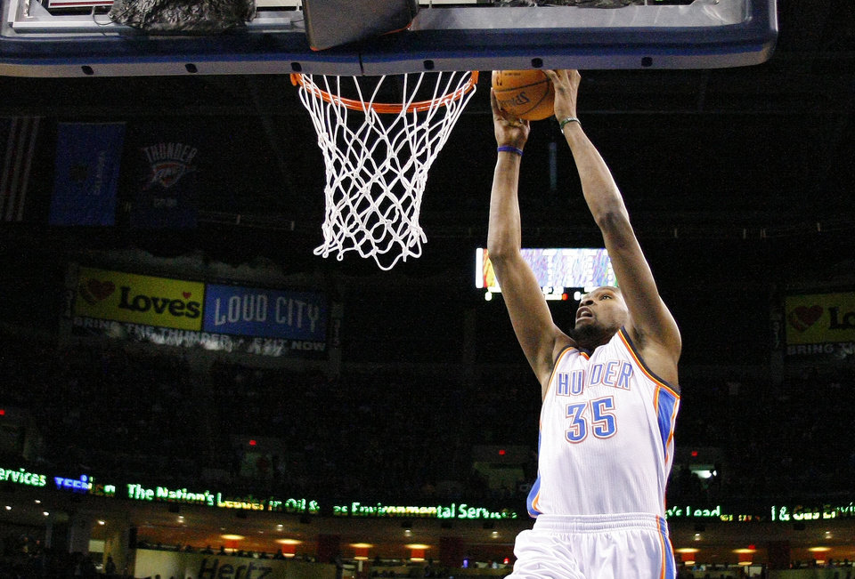 Photo - Oklahoma City Thunder small forward Kevin Durant (35) goes up for a dunk against the Golden State Warriors during the first half of an NBA basketball game Friday, Jan. 17, 2014, in Oklahoma City. (AP Photo/Alonzo Adams)