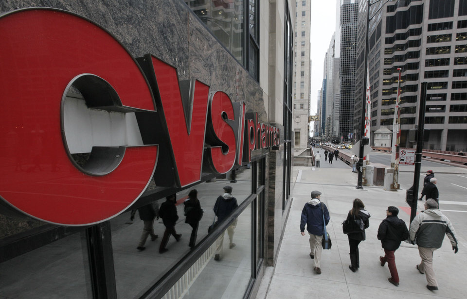 Photo -   In this Feb 7, 2012 photo, pedestrians walk pass a CVS store in Chicago. CVS Caremark Corp.'s fourth-quarter earnings climbed nearly 4 percent, as the drugstore operator's pharmacy services revenue swelled because of a long-term contract and new business. (AP Photo/M. Spencer Green)