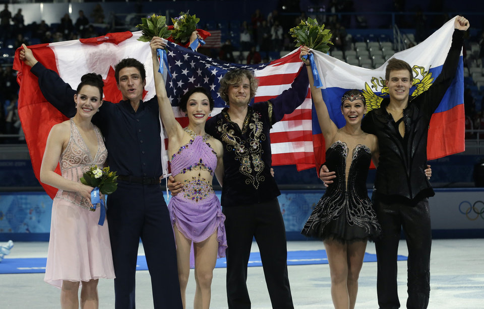 Photo - Meryl Davis and Charlie White of the United States, centre, Tessa Virtue and Scott Moir of Canada, left, and Elena Ilinykh and Nikita Katsalapov of Russia pose for photographers following the flower ceremony for the ice dance free dance figure skating finals at the Iceberg Skating Palace during the 2014 Winter Olympics, Monday, Feb. 17, 2014, in Sochi, Russia. (AP Photo/Darron Cummings)