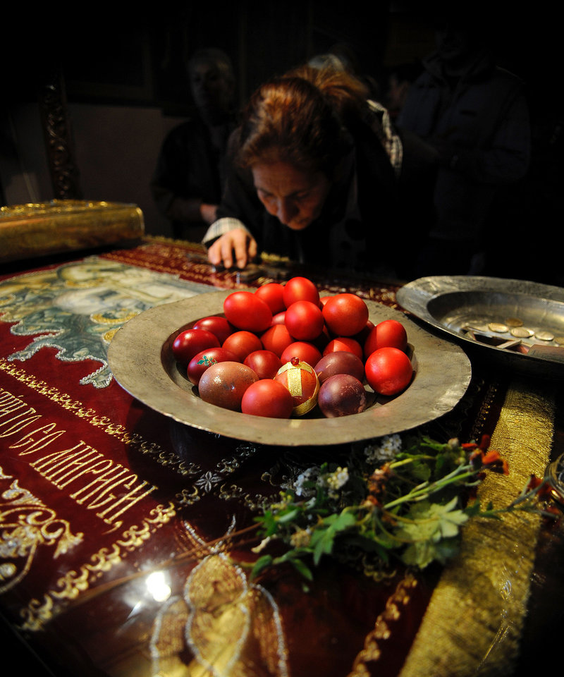 A woman kisses a crucifixion displayed by a dish with Easter eggs on Good Friday, at St Petka Christian Orthodox church in Skopje, Macedonia, on Friday, April 18, 2014. (AP Photo/Boris Grdanoski)