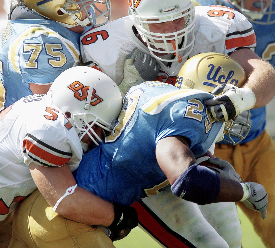 Photo - OSU's defense held UCLA in check in the Cowboys' 31-20 win over the Bruins in OSU's 2004 opener. (Photo by Bryan Terry, The Oklahoman Archive)