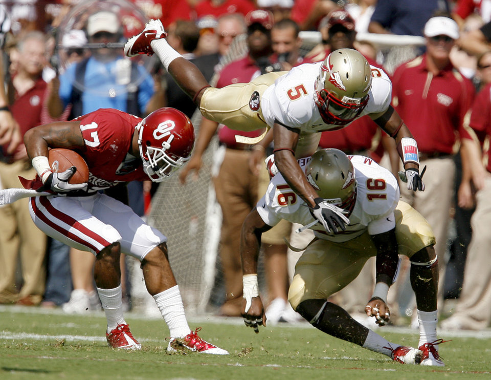 Photo - OU's Mossis Madu gets around Florida State's Greg Reid, top, and Mister Alexander during the first half of the college football game between the University of Oklahoma Sooners (OU) and Florida State University Seminoles (FSU) at the Gaylord Family-Oklahoma Memorial Stadium on Saturday, Sept. 11, 2010, in Norman, Okla.   Photo by Bryan Terry, The Oklahoman ORG XMIT: KOD