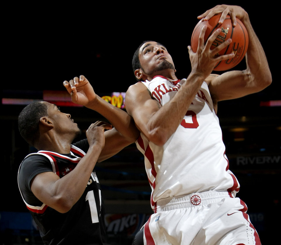 Photo - OU's C.J. Washington grabs the ball in front of Cincinnati's Darnell Wilks during the All-College Classic basketball game between the University of Oklahoma and Cincinnati at the Oklahoma City Arena on Saturday, December 18,  2010.   Photo by Bryan Terry, The Oklahoman