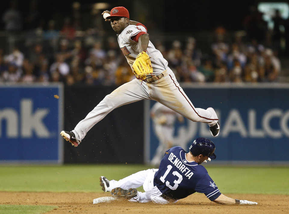 Photo - Arizona Diamondbacks shortstop Didi Gregorius hurdles San Diego Padres' Chris Denorfia while relaying to first during the sixth inning of a baseball game  Saturday, June 28, 2014, in San Diego. Seth Smith was safe at first. (AP Photo/Lenny Ignelzi)