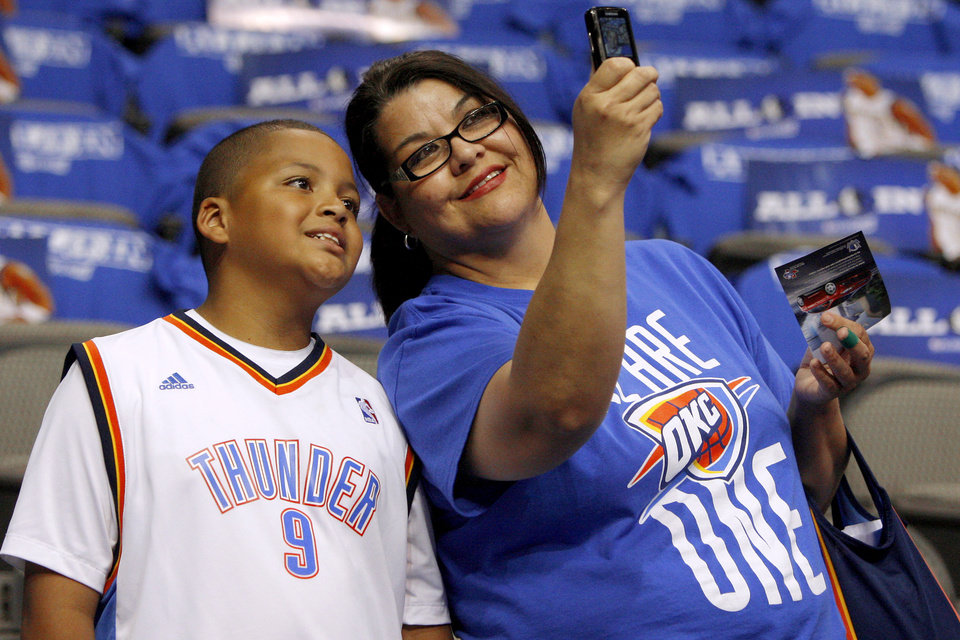 Ninnette Delaune of Anadarko, Okla., takes a picture with her great-nephew Sir\'Darius Smith, 10, before Game 4 of the first round in the NBA playoffs between the Oklahoma City Thunder and the Dallas Mavericks at American Airlines Center in Dallas, Saturday, May 5, 2012. Photo by Bryan Terry, The Oklahoman