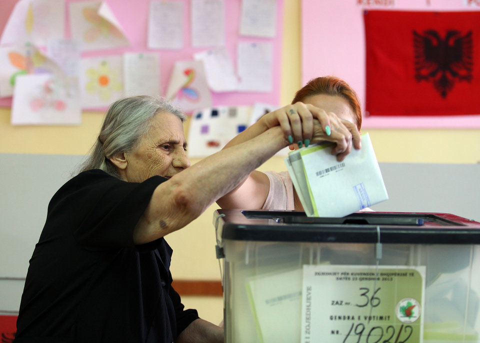 Photo - An Albanian woman casts her vote in Tirana, Sunday, June 23, 2013 in the Albanian elections. An Albanian political candidate was shot and a supporter of a rival party killed in an exchange of gunfire near a polling station, police said Sunday, as the country held crucial elections already marred by a dispute that could leave the outcome up in the air. Both conservative Prime Minister Sali Berisha and his close rival, Socialist leader Edi Rama, have hopes for eventual entry to the European Union, and the election is seen as a test of whether the country can run a fair and safe vote. (AP Photo/Hektor Pustina)