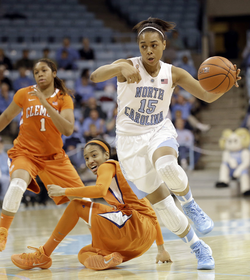Photo - North Carolina's Allisha Gray (15) dribbles past Clemson's Chancie Dunn and Charmaine Tay (1) during the first half of an NCAA college basketball game in Chapel Hill, N.C., Thursday, Jan. 16, 2014. (AP Photo/Gerry Broome)