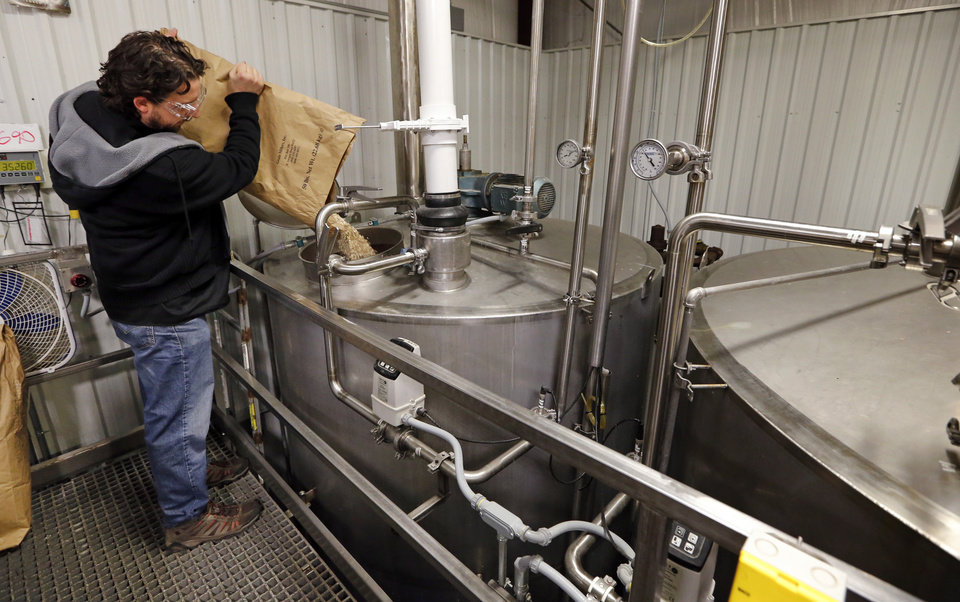 Photo -  Dave Monk with Iron Monk Brewing Co. of Stillwater, pours grain into a stainless steel container to make a mash as craft brewers gathered to make a special beer to promote the modernization of Oklahoma's alcohol laws on Jan. 19, 2016 in Krebs. [Photo by Steve Sisney, The Oklahoman Archives]