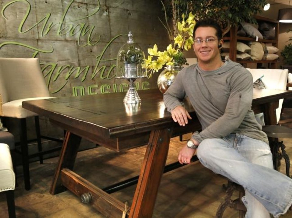 Photo -  Jason Thomas shows one of the tables his company made from reclaimed wood at