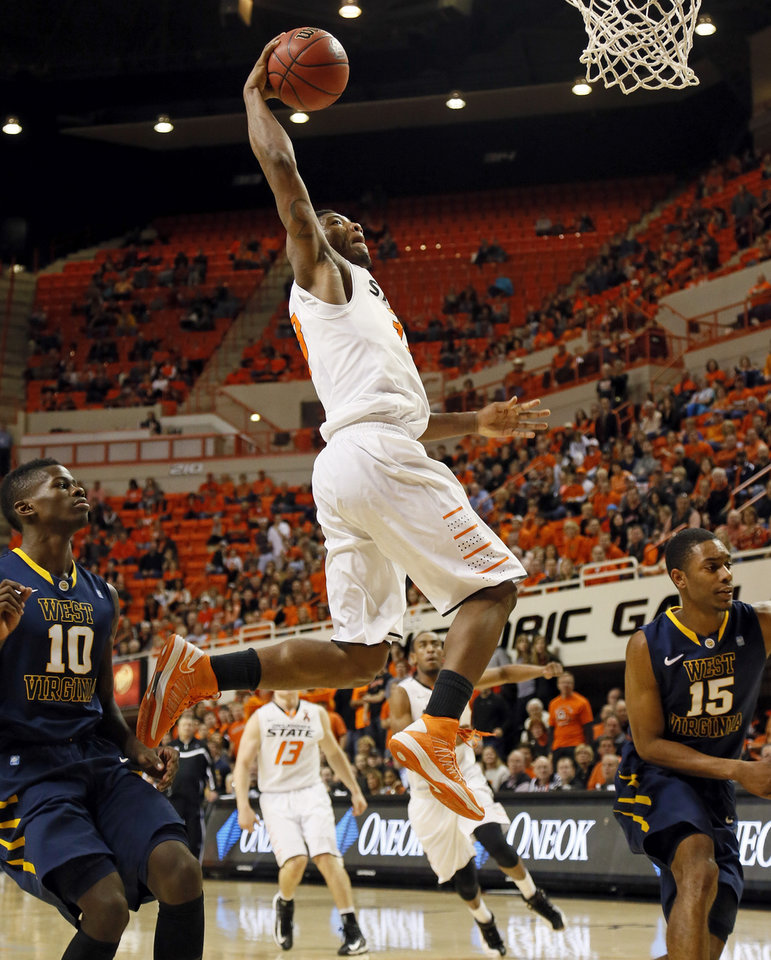 Photo - Oklahoma State's Marcus Smart (33) dunks the ball during an NCAA men's basketball game between Oklahoma State University (OSU) and West Virginia at Gallagher-Iba Arena in Stillwater, Okla., Saturday, Jan. 26, 2013. Oklahoma State won, 80-66. Photo by Nate Billings, The Oklahoman