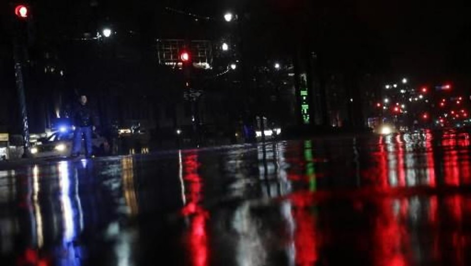 Lights are reflected on Canal Street as a police officer patrolling the area passes a pedestrian as storm bands from Hurricane Isaac hit, Tuesday, Aug. 28, 2012, in New Orleans, Louisiana. Isaac, a massive storm spanning nearly 200 miles from its center, made landfall Tuesday evening near the mouth of the Mississippi River. (AP Photo/Eric Gay)