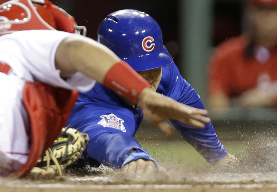 Photo - Chicago Cubs' Anthony Rizzo, right, tags home plate ahead of the tag by Cincinnati Reds catcher Brayan Pena in the fifth inning of a baseball game on Wednesday, April 30, 2014, in Cincinnati. Rizzo scored on a sacrifice fly by Nate Schierholtz. (AP Photo)