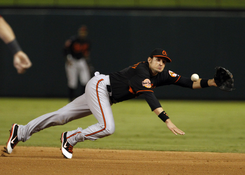 Baltimore Orioles second baseman Ryan Flaherty can't stop a single by Texas Rangers' Michael Young during the fourth inning of an American League wild-card playoff baseball game Friday, Oct. 5, 2012 in Arlington, Texas. (AP Photo/Tony Gutierrez)
